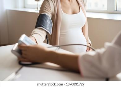 Arzt, der den Blutdruck ihrer schwangeren Patientin misst. Hochwertiges Foto