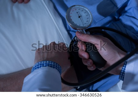 Doctor is measuring blood pressure of his patient