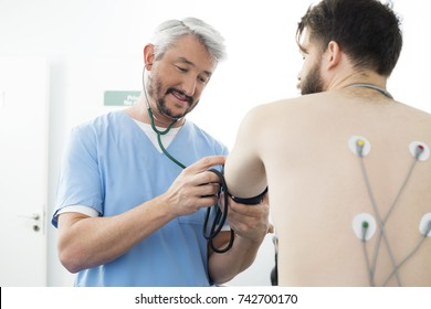 Doctor Measuring Blood Pressure Of Patient In Hospital