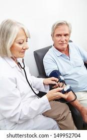 Doctor measuring blood pressure of senior patient in hospital