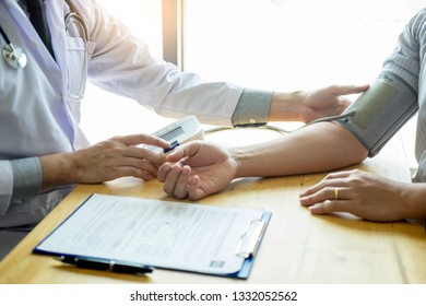 Doctor measuring and checking blood pressure of patient in hospital, Health care concept