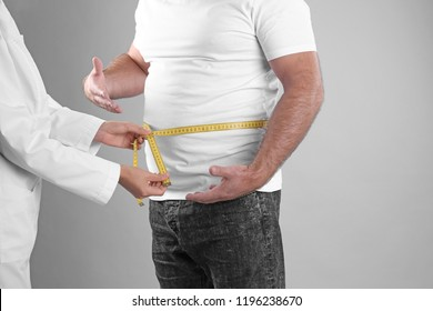 Doctor measuring fat man's waist on grey background. Weight loss