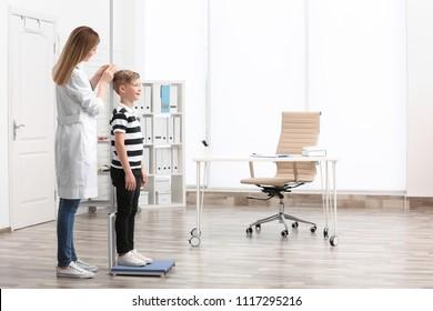 Doctor measuring little boy's height in hospital