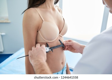 Doctor measuring proportion of body of woman with calipers