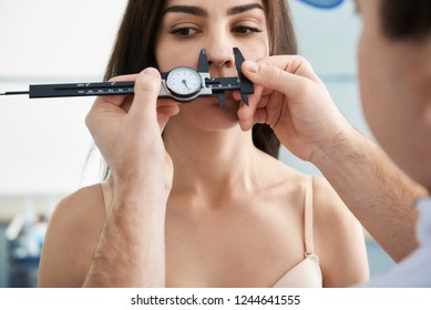 Doctor measuring proportions of female nose while using calipers