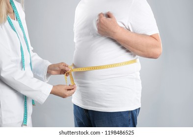 Doctor measuring senior man's waist on grey background. Weight loss