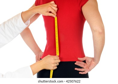 A doctor is measuring the spine of a young woman