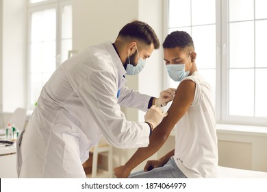 Doctor in medical face mask giving injection to patient during vaccination campaign at the clinic. Young African-American man getting Covid-19, AIDS or flu antivirus vaccine shot at the hospital