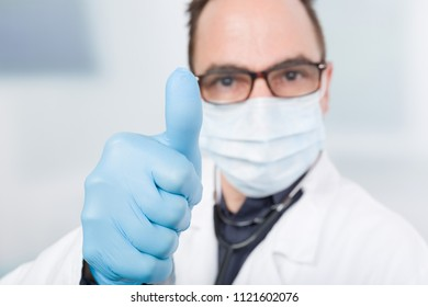 doctor with medical face mask and medical gloves shows thumb up