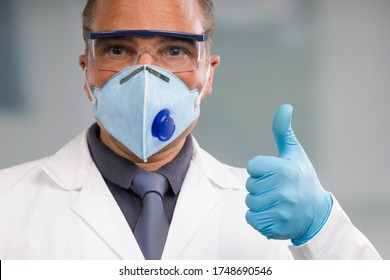 Doctor with medical face mask and medical gloves shows thumbs up