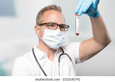 doctor with medical face mask is holding a blood probe in laboratory
