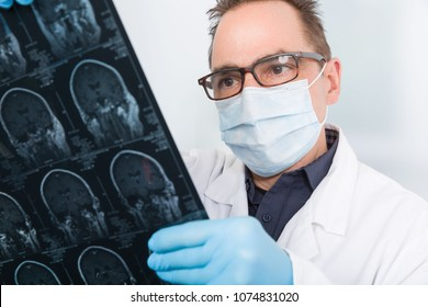 Doctor with medical face mask is looking on an x-ray image