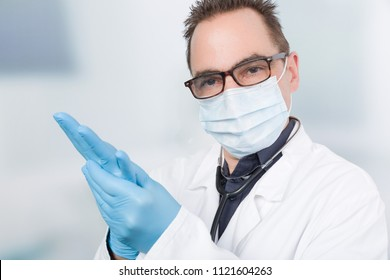 doctor with medical face mask puts on  medical gloves