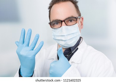 doctor with medical face mask using medical gloves and shows thumb up