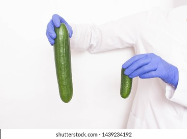 A doctor in medical gloves holds two different sized cucumbers. Concept of increasing penis in men, viagra