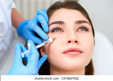 Doctor in medical gloves with syringe injects botulinum under eyes for rejuvenating wrinkle treatment. Filler injection for eye wrinkles smoothing. Plastic aesthetic facial surgery in beauty clinic