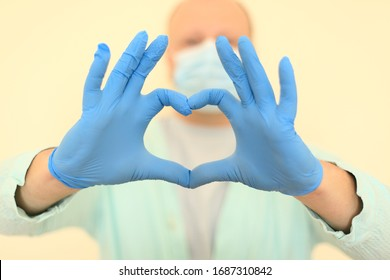 Doctor in medical mask and gloves shows heart gesture, covid-19 virus treatment, pandemic response
