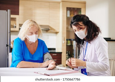 Doctor in medical mask visiting female senior patient, checking her blood pressure and filling medical history