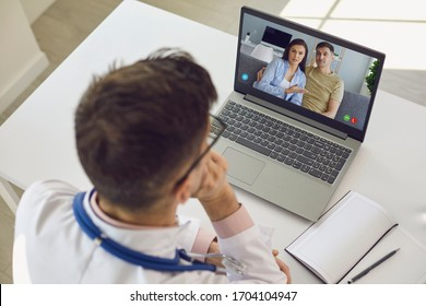Doctor medical online call.Shoulder view doctor therapist psychologist speaks with couple video chat using a laptop in a clinic office.