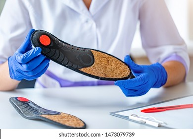 Doctor in medical rubber gloves holds an orthopedic insole for treatment and prevention of flat feet during medical consultation. Foot сare and comfortable wearing shoes