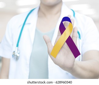 Doctor with medical stethoscope hold ribbon colors yellow (Marigold), blue and purple for Bladder Cancer Awareness Month in May