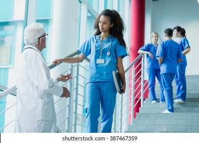 Doctor and medicine student talking on hospital stairs, in the background group of trainees in blue uniforms