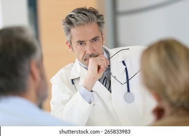 Doctor meeting couple in hospital office