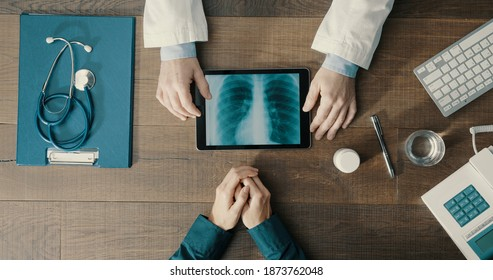Arzt, der einen Patienten im Büro trifft und eine ärztliche Beratung durchführt, benutzt er eine digitale Tablette und überprüft medizinische Unterlagen
