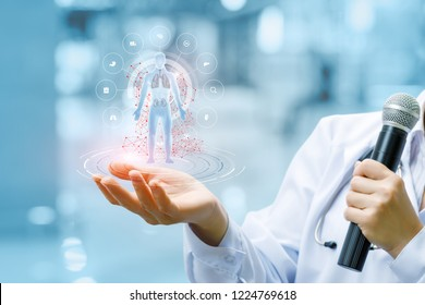 A doctor with a microphone is holding a digital figure with internal organs images inside surrounded . The concept is the development and new technologies of morden medicine.