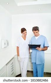 Doctor next to nurse checks medical record on clipboard