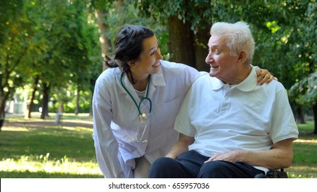 Doctor, nurse, care for the elderly, girl (woman) and grandfather sitting in a wheelchair, walking in the park. Concept: a boarding house, a sanatorium, a house for the elderly, help for the elderly.