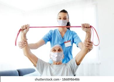 Pflegeübungen von Ärzten oder Krankenschwestern mit Senioren, die Masken zu Hause tragen