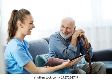 Pflegepersonal mit Senioren, die sich Fotoalbum und Bild zu Hause oder im Pflegeheim ansehen