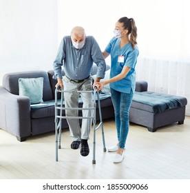 Betreuer des Arztes oder der Krankenschwester mit Senioren, die zu Hause oder zu Hause eine Gehhilfe in Form einer Gehhilfe in Anspruch nehmen