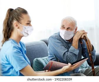 Pflegepersonal für Ärzte oder Krankenschwestern mit Schutzmasken, die Fotoalbum und Bild zu Hause oder zu Hause ansehen