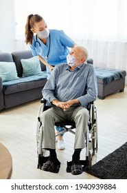 Doctor or nurse caregiver with senior man in a wheelchair wearing protective masks at home or nursing home