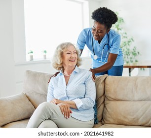 Doctor or nurse caregiver with senior woman at home or nursing home