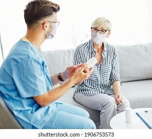 Ärztin oder Pflegepersonal, die Senioren zu Hause oder im Pflegeheim eine Medikamentenflasche zeigt, mit Schutzmasken