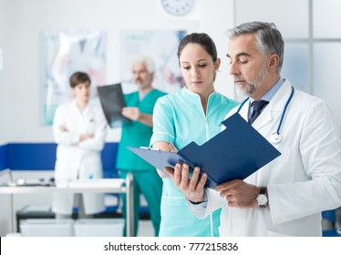 Doctor and nurse examining patient's medical records and medical team working on the background
