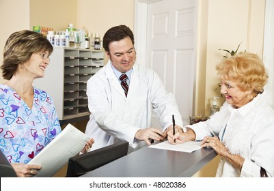 Doctor and nurse greating a new patient as she signs in.  Focus on doctor.