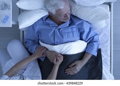 Doctor or nurse holding hand of senior male patient lying in hospice bed