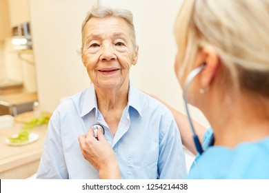 Doctor or nurse listens to elderly woman with a stethoscope at home visit