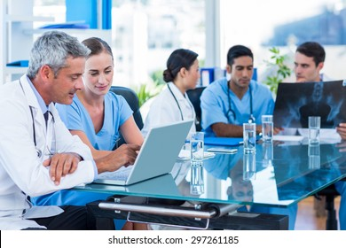 Doctor and nurse looking at laptop with colleagues behind in medical office