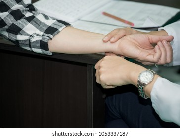 Doctor or nurse measuring patient pulse,Yearly check measure pulse – patient hand checking for a radial pulse for a minute,Female doctor checking patient pulse,Medical checking in hospital,