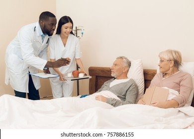 A doctor and a nurse offer an elderly couple an apple, marshmallows and muffins to bed. At this time, the man is dripping a medical dropper. The nurse has a tray with food in her hands.