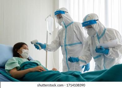 zwei Ärzte in persönlicher Schutzausrüstung oder ppe Behandlung der asiatischen Patientin mit Covid-19-Infektion oder Coronavirus-Infektion in der Isolationseinheit im Krankenhaus während der Pandemie. medizinisches Konzept