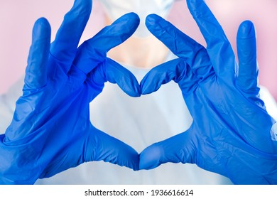 Doctor or nurse in protective gloves shows the symbol of the heart. Doctor care and love concept to patients. Love, care and safety symbol. Close-up.