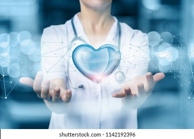 Doctor or nurse protects heart on blurred background.