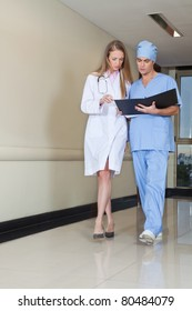 Doctor and nurse reading file while walking in hospital
