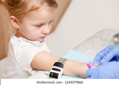 Doctor or nurse ready to take a blood sample from little girl's arm vein with a vacutainer. Pediatric venipuncture or venepuncture procedure. Focus on a tourniquet